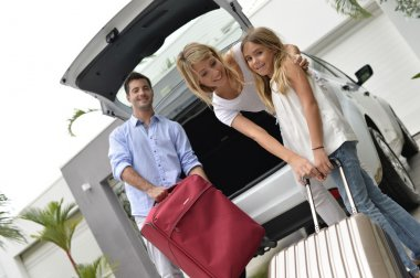 Parents with child putting luggage in car trunk
