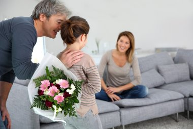 Girl offering flowers to mom
