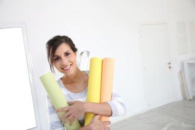 Girl holding wallpaper rolls