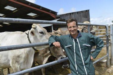 Farmer leaned on fence by barn