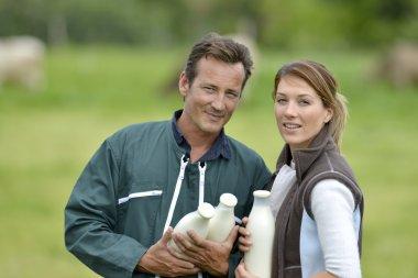 Farmers holding milk bottles