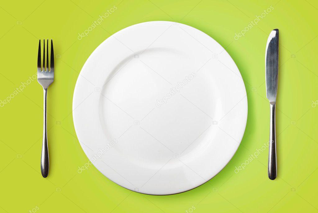 Prato vazio garfo e faca sobre fundo verde fotografias for Plato tenedor y cuchillo
