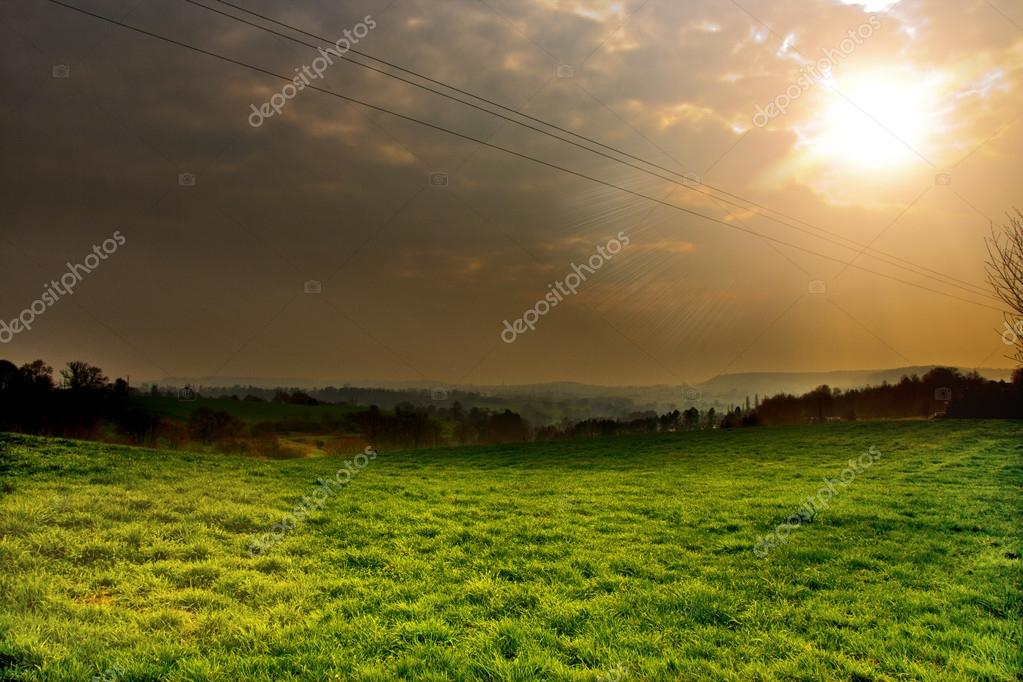 Sunset above the green fields