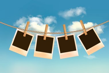 Retro photos hanging on a rope in front of a blue sky with cloud