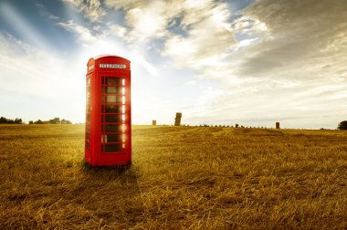 Old-fashioned traditional red telephone booth or public payphone standing in an open deserted field in evening light stock vector
