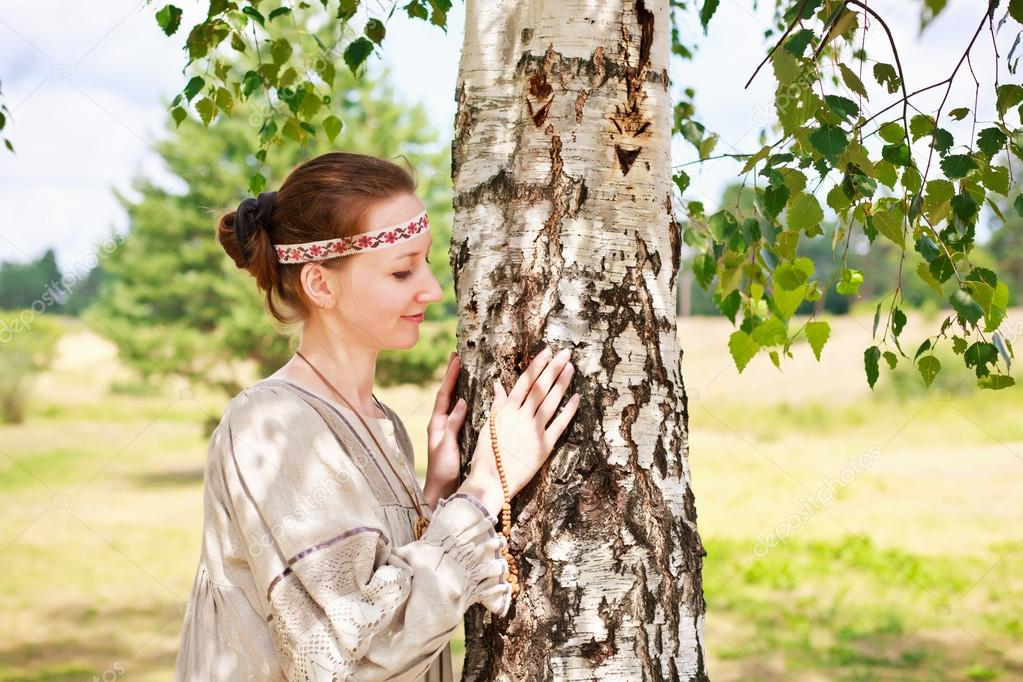 Woman next to the green birch