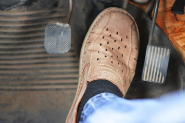 Mans feet pushing on the accelerator of automobile