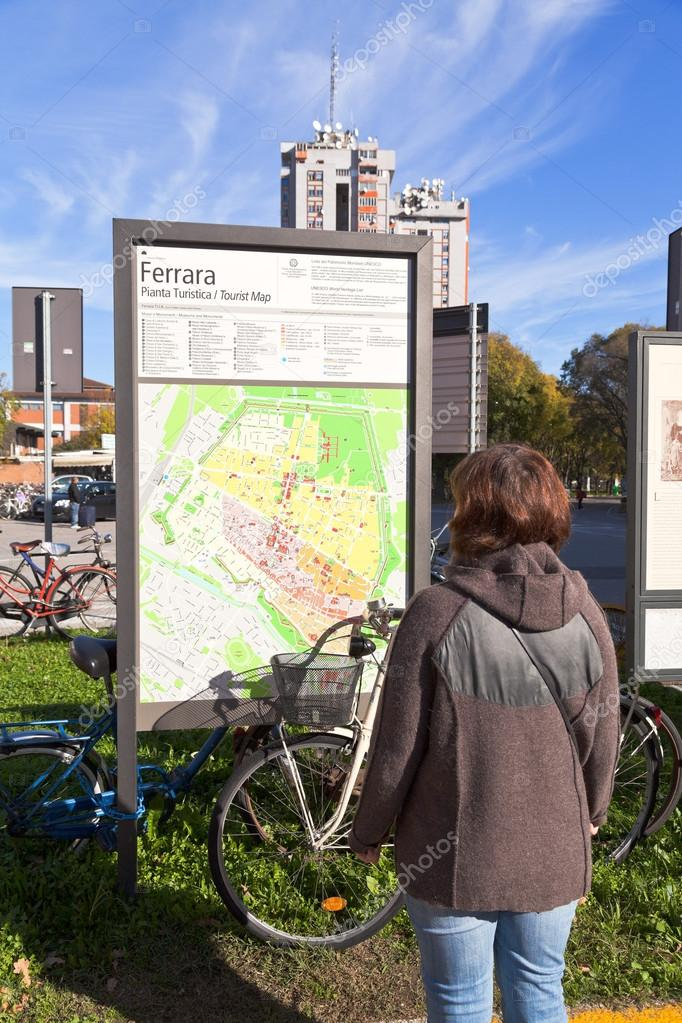 Tourist near Ferrara city map and bicycle Stock Editorial Photo