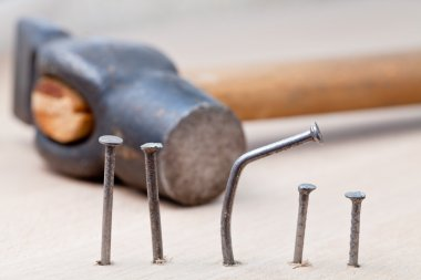 hammer nails into wooden board
