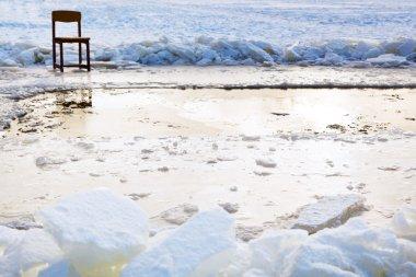 icebound chair near ice hole in frozen lake
