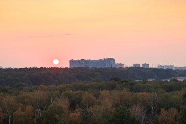sun during red sunrise over houses and urban park