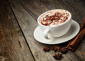 Photo coffee cup and beans, cinnamon sticks, nuts and chocolate on woo