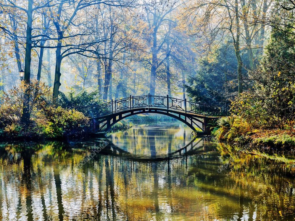 Autumn - Old bridge in autumn misty park