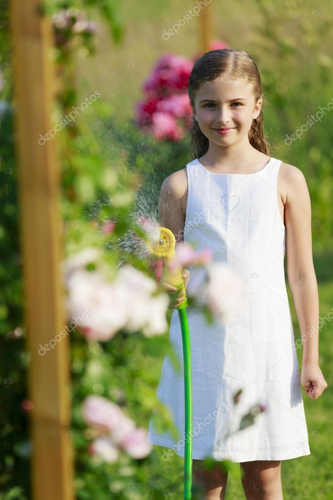 Summer garden, watering - beautiful  girl watering roses