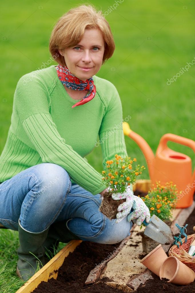 Gardening, planting - woman planting flowers in the garden