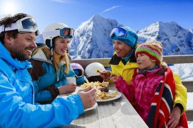 Winter, ski - skiers enjoying lunch in winter mountains
