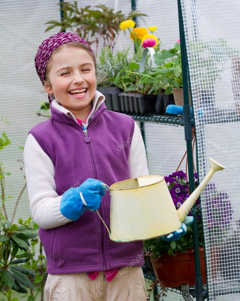Gardening, planting concept - lovely girl watering flowers in the greenhouse