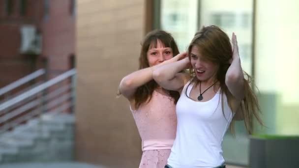 due amiche si divertono con i loro capelli su una strada