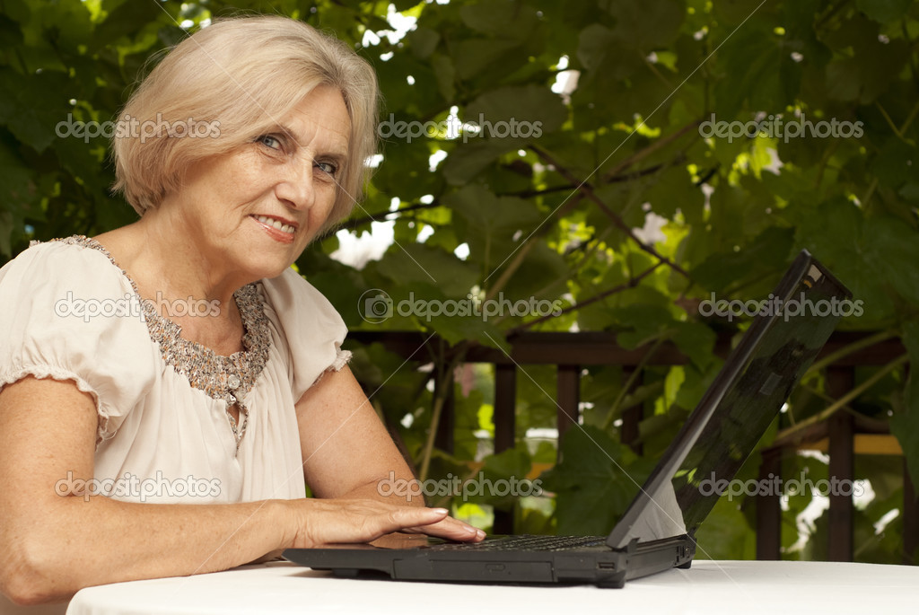 1c472155 Sweet older woman sitting at a table at home on the veranda — Photo by ...