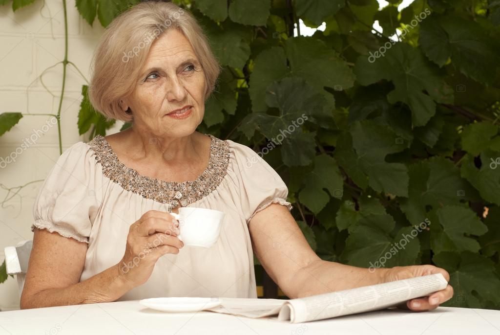97baeda7 Cute older woman sitting at a table at home on the veranda — Photo by ...