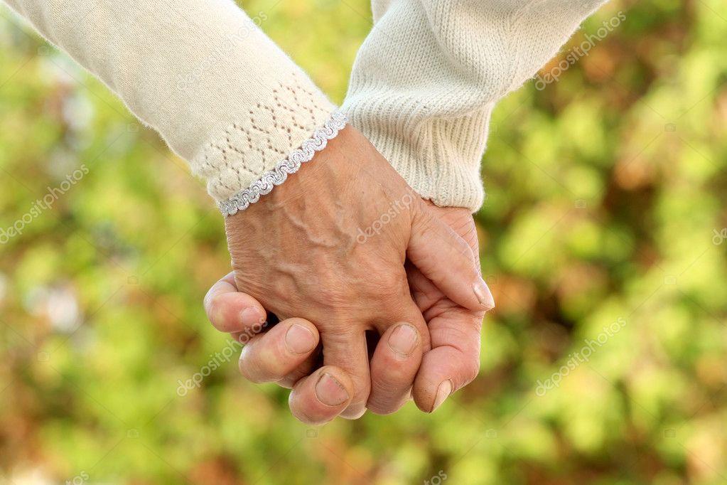 Älteres Ehepaar hält Händchen - Stockfotografie
