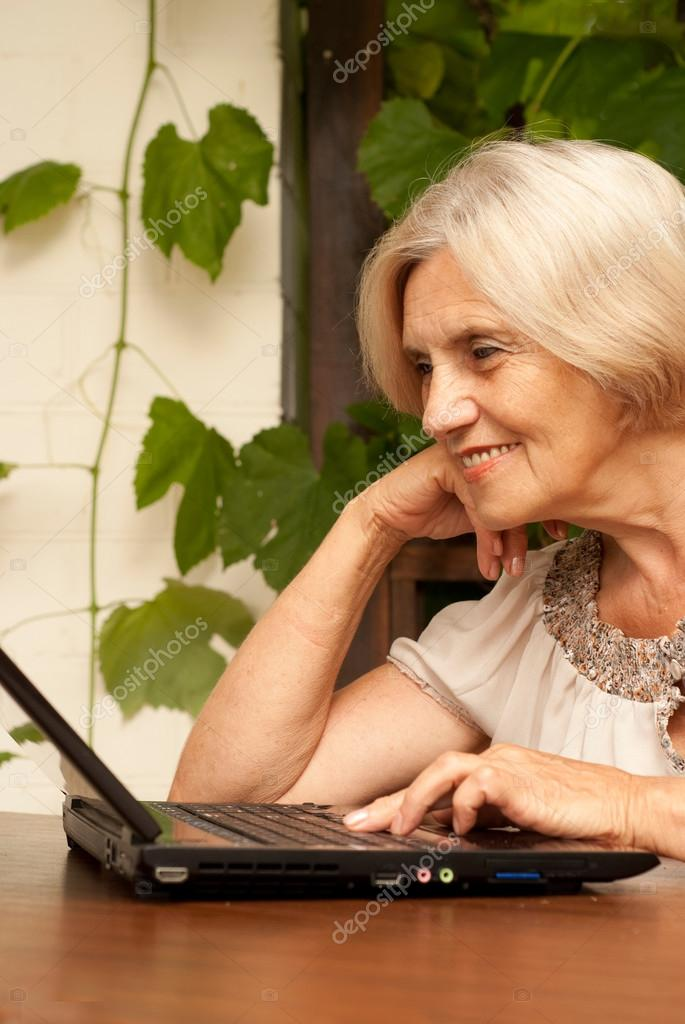 ff361a7d Attractive older woman sitting at a table at home on the veranda — Photo by  ...
