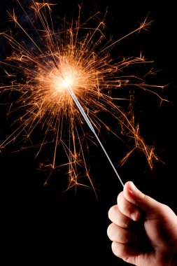 Child's hand, holding a burning sparkler.