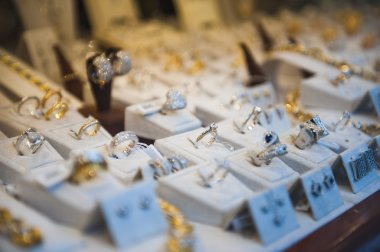 Window display at jewelry shop presenting necklace, rings and earring sets. Tilt-shift lens used to accent the specific objects and to emphasize the attention on it. stock vector
