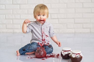 Kid eating strawberry jam