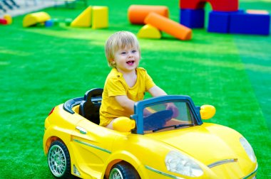 Kid in the yellow car on the playground