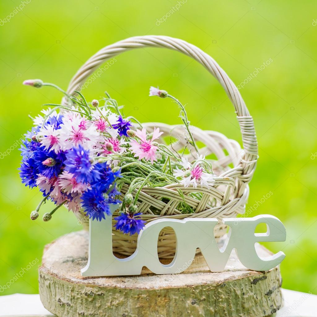 Beautiful Flowers In The Basket And Word Love Stock Photo