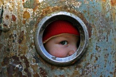 Kid looking through the round window