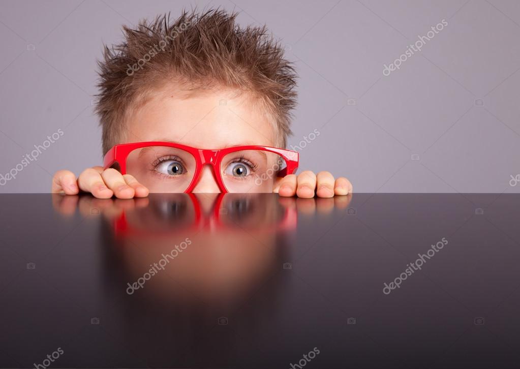 cute boy hiding behind a table