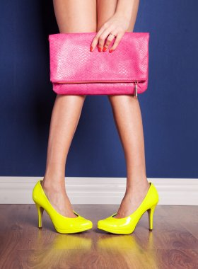 A woman showing off her yellow high heels and pink bag