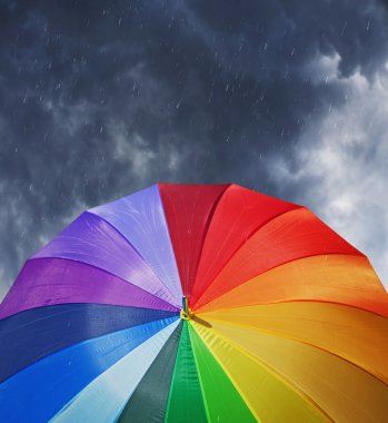 Rainbow umbrella on dramatic sky background