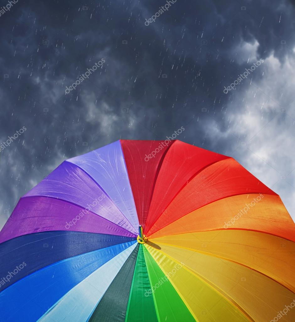 Rainbow umbrella on dramatic sky background