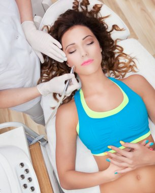 Woman getting face laser treatment