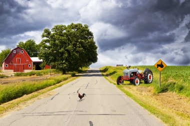 Country Road With Red Barn and Tractor On Side
