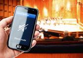 ruka držící smartphone s ztlumení zvuku při koncertu