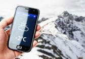 ruka držící smartphone se počasí v horách