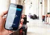 ruka držící smartphone s wi-fi připojení v kavárně