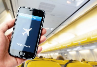 Hand holding smartphone inside the plane