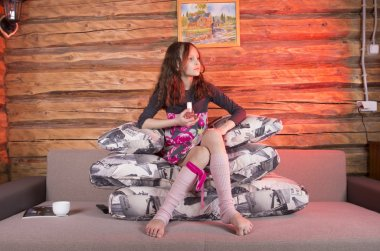 little girl playing at sofa with pillows