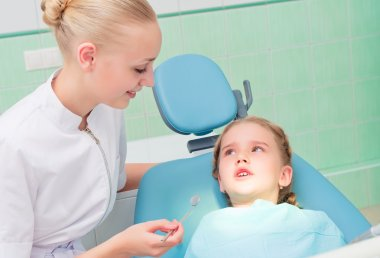 Young doctor woman and girl in dentist office