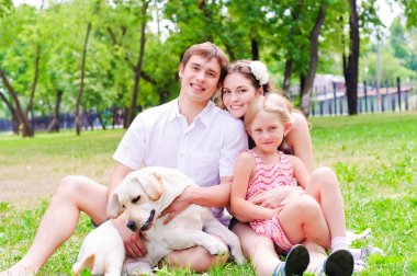 Happy young family with Labrador