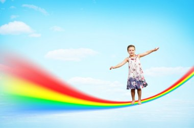Girl jumping on clouds and a rainbow