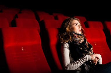 Young attractive woman sitting in a cinema