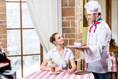 Chef brings a dish pretty woman in a restaurant
