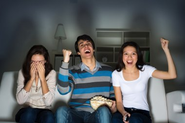 group of young watching TV on the couch