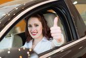 mladá žena v autě a ukazuje palec